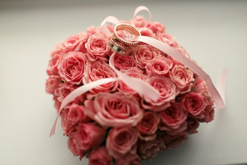 תמונה של סידור פרחים לחתונה עליו מונחות טבעות נישואין
